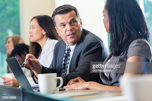 mature businessman attending seminar or conference with african american colleague - attending stock pictures, royalty-free photos & images