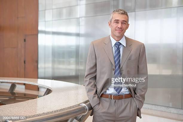 Mature businessman beside desk in lobby, hands in pockets, portrait