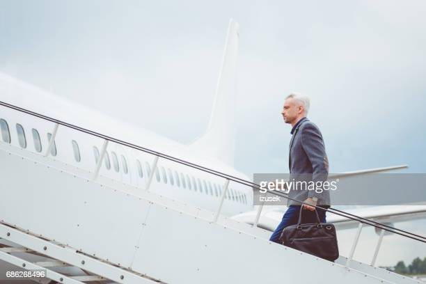 Mature businessman boarding airplane