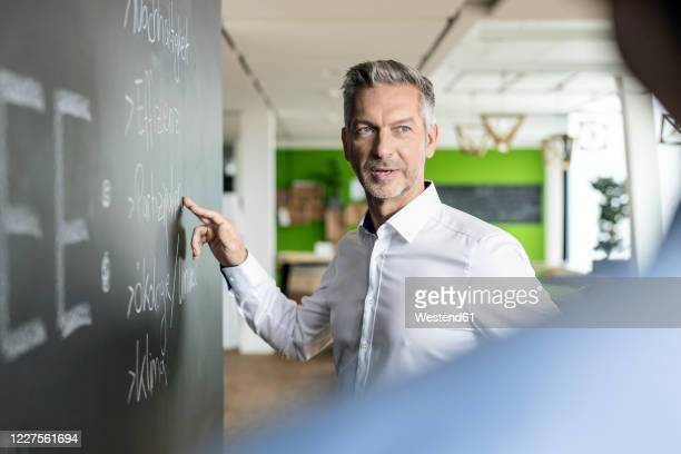 mature businessman brainstorming at blackboard in office - instructor stock pictures, royalty-free photos & images
