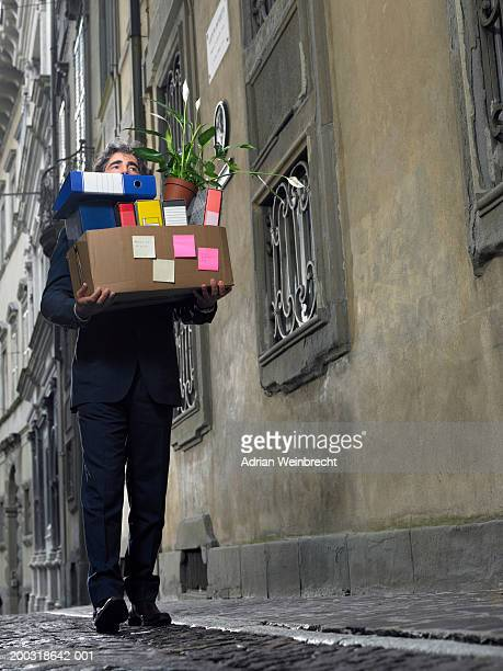 Mature businessman carrying box of office files in street