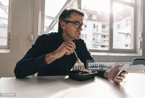 mature businessman checking cell phone during lunch break in office - aufwärmen stock-fotos und bilder