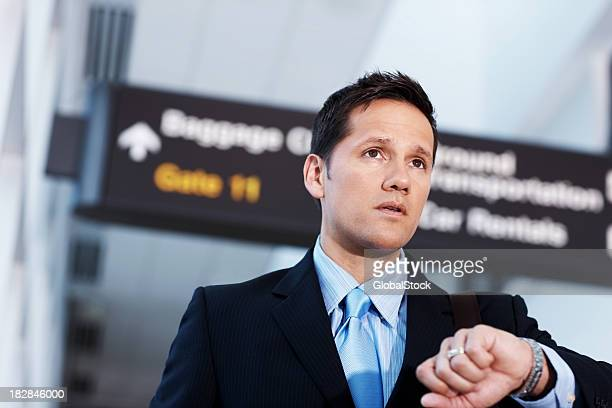 Mature businessman checking time at the airport