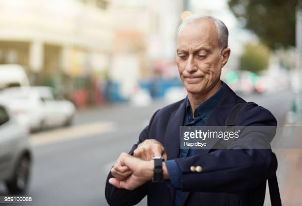 rijpe zakenman controleert zijn horloge in stedelijke straat - ongeduldig stockfoto's en -beelden