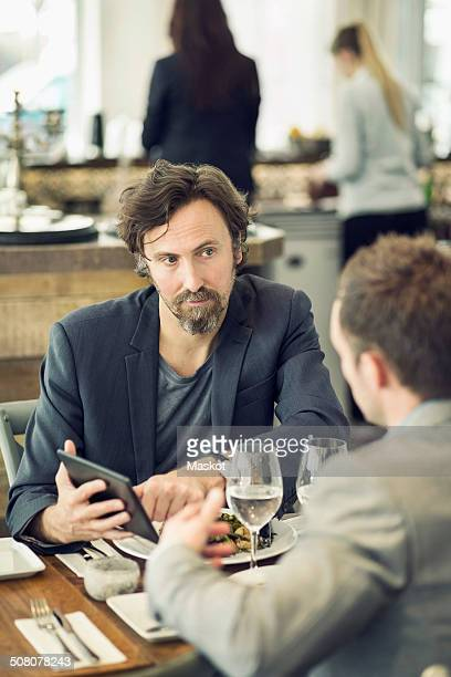 Mature businessman discussing over digital tablet with colleague at restaurant table