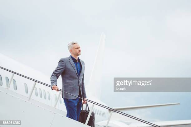 empresario maduro desembarcar el avión - movimiento hacia abajo fotografías e imágenes de stock