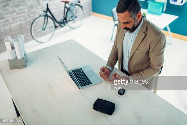 mature businessman doing blood sugar test in his office - glucose stock pictures, royalty-free photos & images