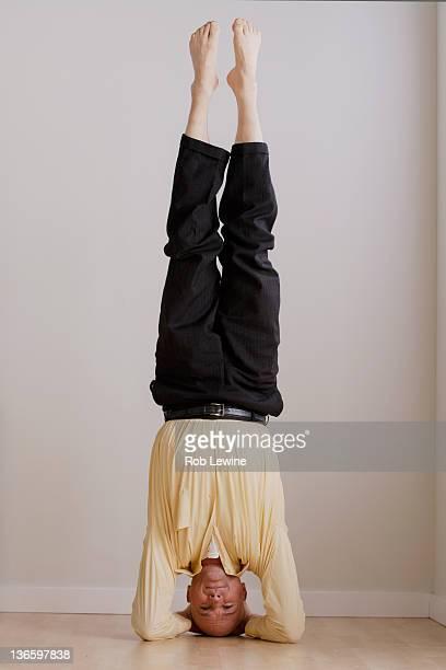 Mature businessman doing headstand