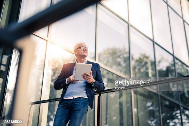 mature businessman doing work on tablet outside of an office building. - looking away stock pictures, royalty-free photos & images