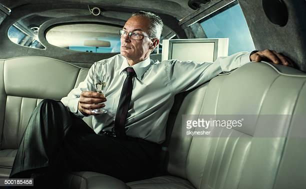 Homme d'affaires d'âge mûr boire du champagne dans une limousine.