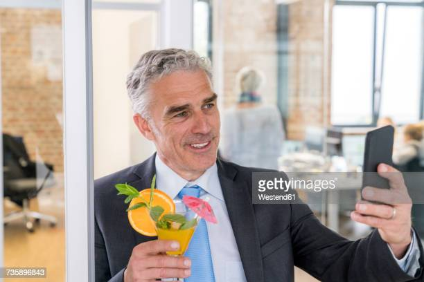 Mature businessman drinking cocktail while taking a selfie