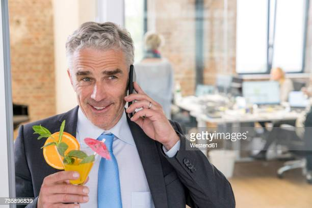 Mature businessman drinking cocktail while talking on the phone