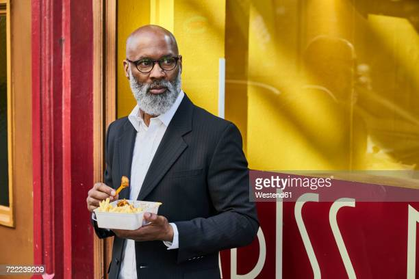 mature businessman eating french fries in front of snack bar - fries stock-fotos und bilder