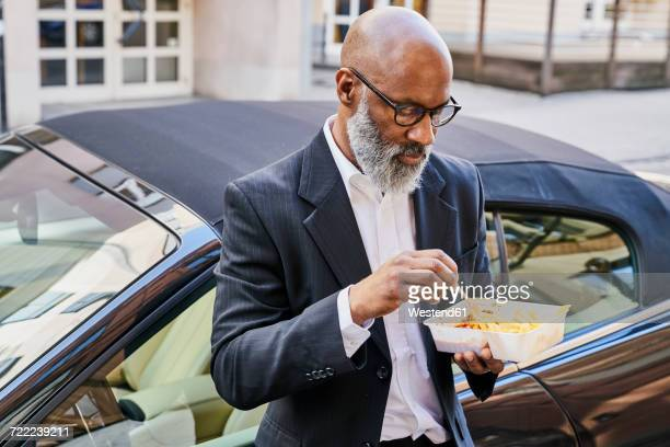 Mature businessman eating French fries