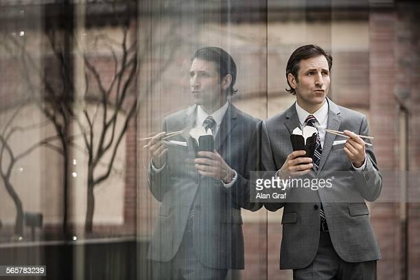 mature businessman, eating lunch from takeaway box, outdoors - symmetrie stockfoto's en -beelden