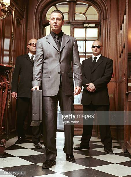 Mature businessman entering hallway, two security guards standing behind