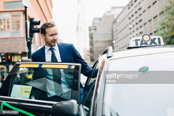 mature businessman entering taxi in city - 入る ストックフォトと画像