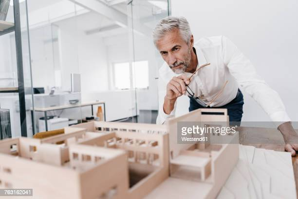mature businessman examining architectural model in office - architectural model stock pictures, royalty-free photos & images