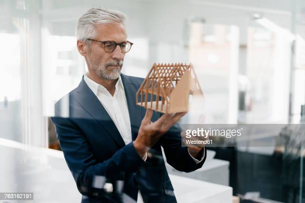 mature businessman examining architectural model in office - architect stockfoto's en -beelden