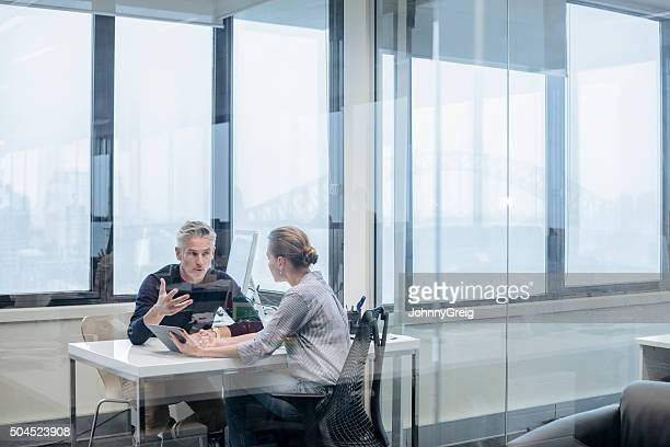mature businessman explaining to business colleague in office - discussion stock photos and pictures