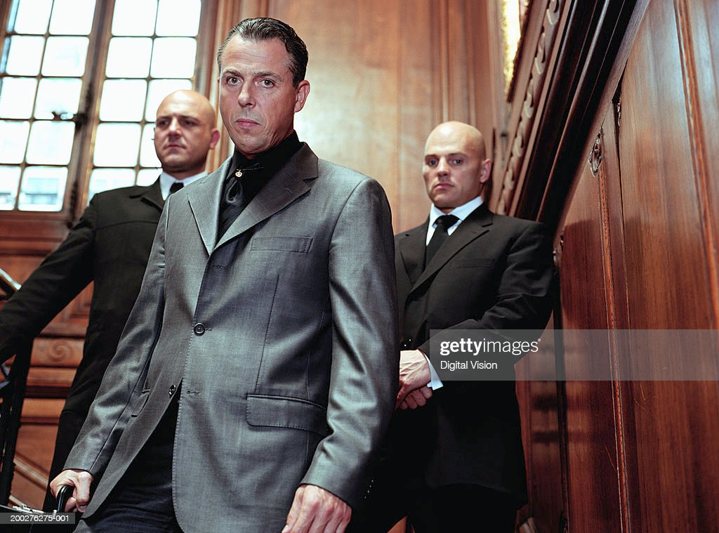 Mature businessman flanked by two security guards in panelled room, portrait : Stock Photo