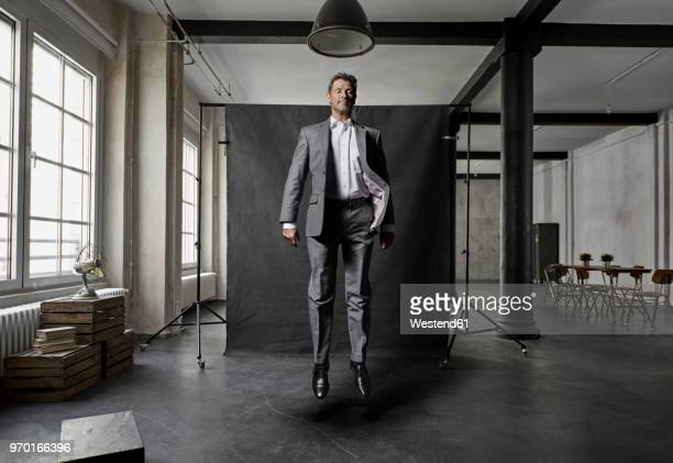 mature businessman floating in front of black backdrop in loft - hovering stock pictures, royalty-free photos & images