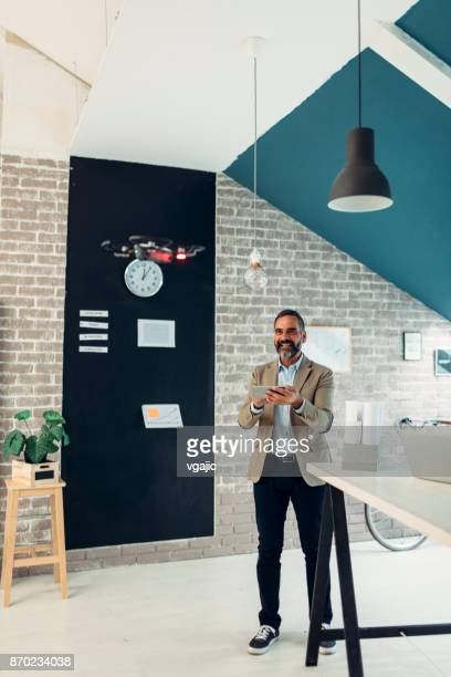 mature businessman flying a drone in his office - remote controlled stock photos and pictures