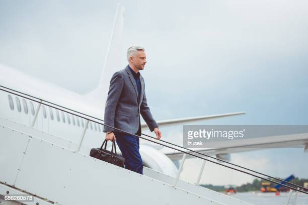 Mature businessman getting out of airplane