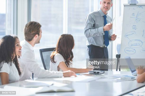 Mature Businessman giving a presentation to his team.