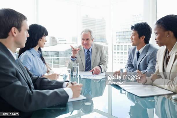 Reifer Geschäftsmann gibt Erklärungen zu seiner jüngeren Mitarbeiter