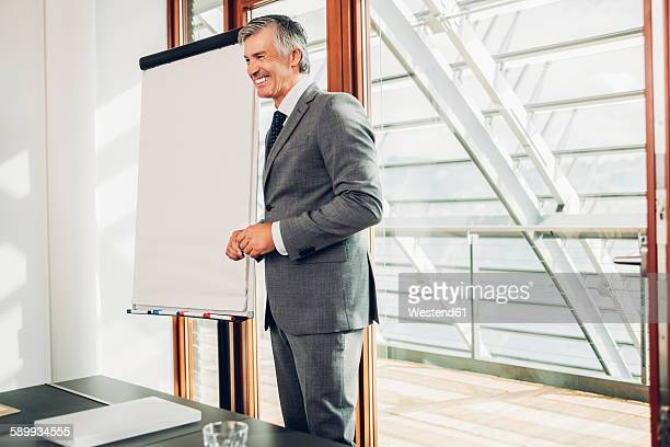 Mature businessman giving presentation in office