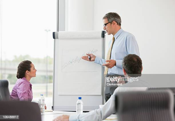 mature businessman giving presentation to colleagues in office - chairperson stock pictures, royalty-free photos & images