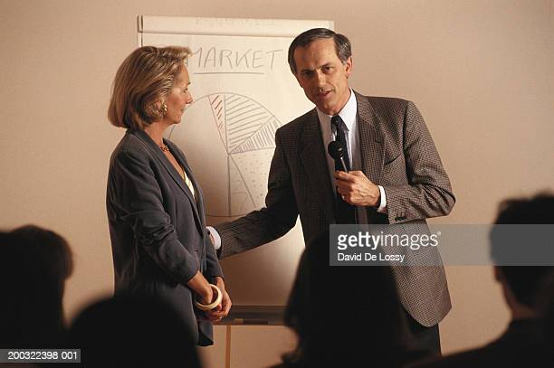 Mature businessman greeting mature businesswoman in front of colleagues