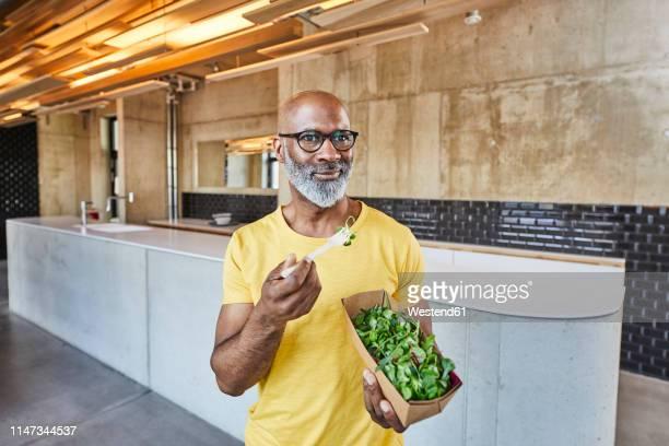 Mature businessman having a salad in modern office