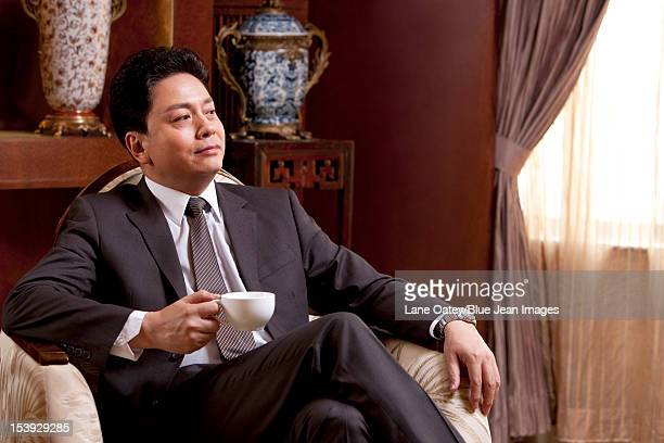 Mature businessman having coffee in a luxurious room