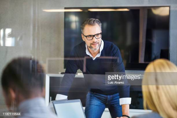 mature businessman having discussion in meeting room - mid adult women stock pictures, royalty-free photos & images