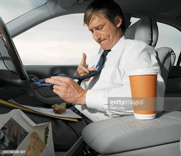 Mature businessman having lunch in car, wiping tie with finger