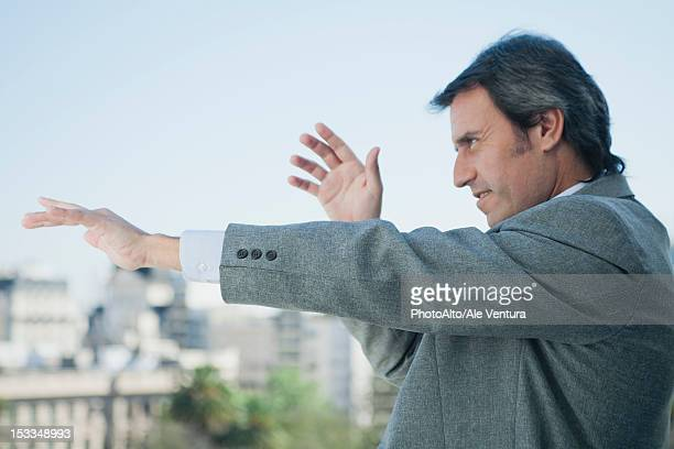 mature businessman holding arms out in front of him and pointing, looking out of frame - out of frame stock pictures, royalty-free photos & images