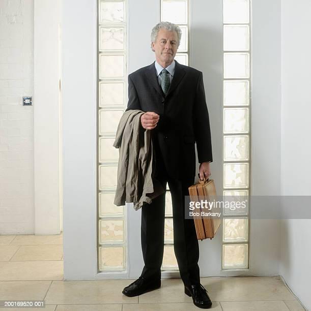 Mature businessman holding briefcase, coat over arm, portrait