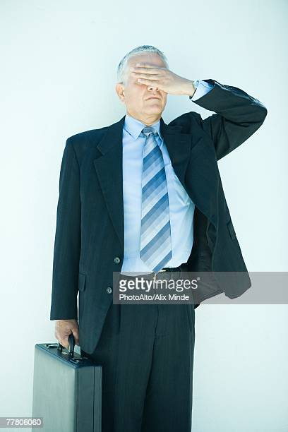 mature businessman holding briefcase, hand covering eyes, three quarter length - see no evil hear no evil speak no evil stock pictures, royalty-free photos & images