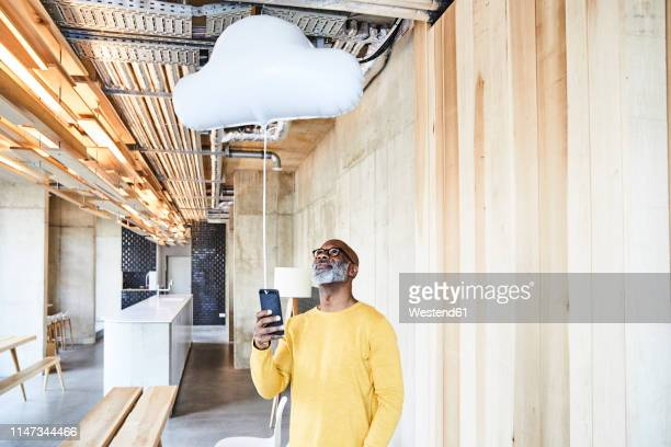 mature businessman holding cell phone attached to cloud balloon - cloud computing stock-fotos und bilder
