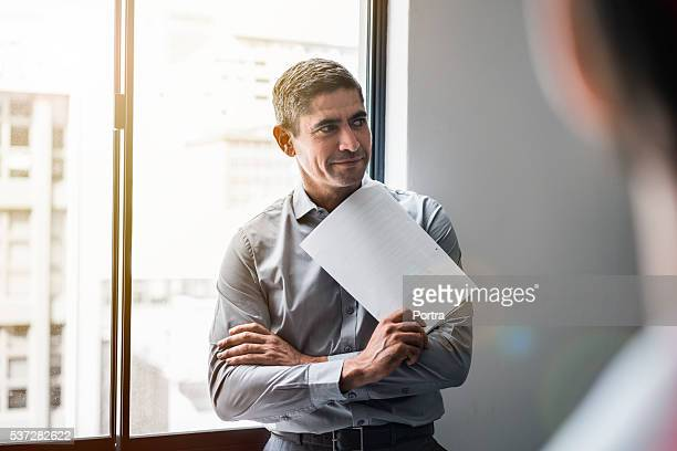 mature businessman holding document in meeting - 40 49 jaar stockfoto's en -beelden