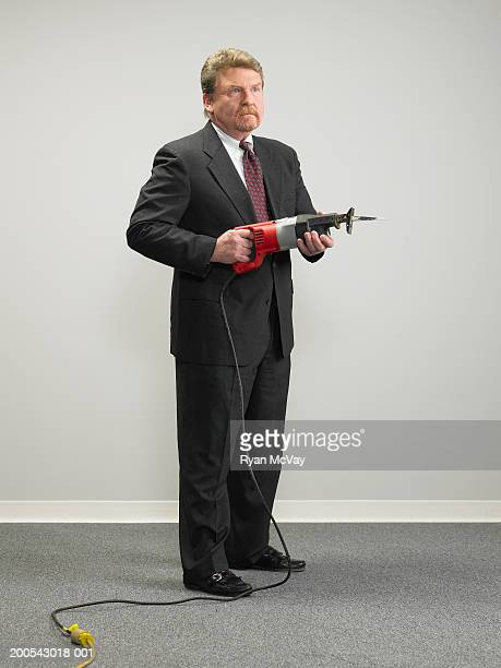 Mature businessman holding electric saw, looking away