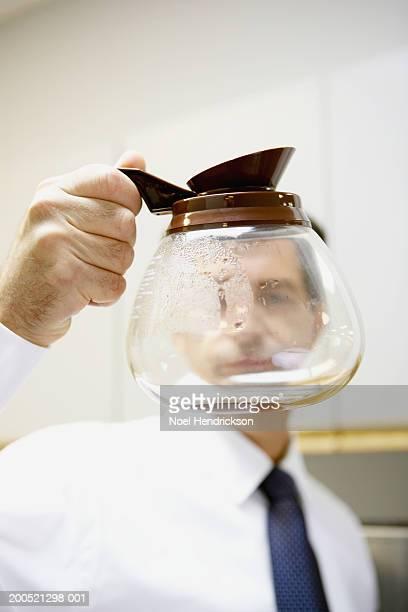 Mature businessman holding holding empty coffee pot, close-up