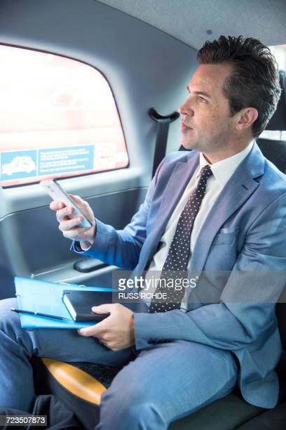 Mature businessman holding smartphone in taxi cab