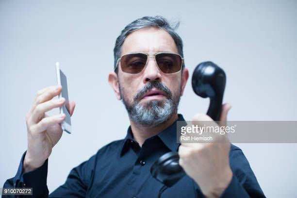 Mature businessman holding telephone receiver and mobile phone against white background