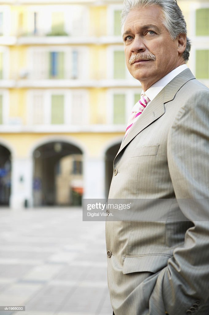 Mature Businessman in a Smart Grey Suit Stands in a Courtyard : Stock Photo