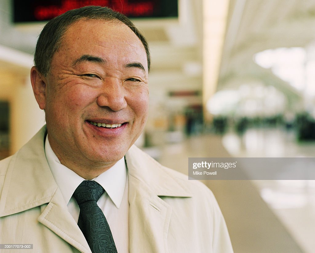 Mature businessman in airport, smiling : Stock Photo