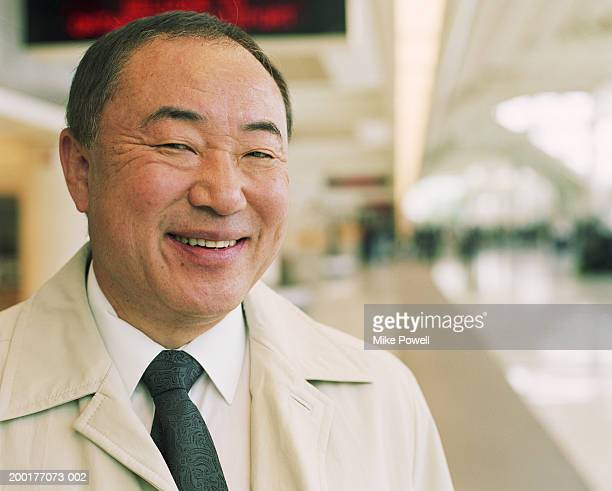 Mature businessman in airport, smiling