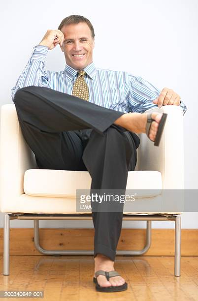 Mature businessman in chair wearing thong sandles, smiling, portrait